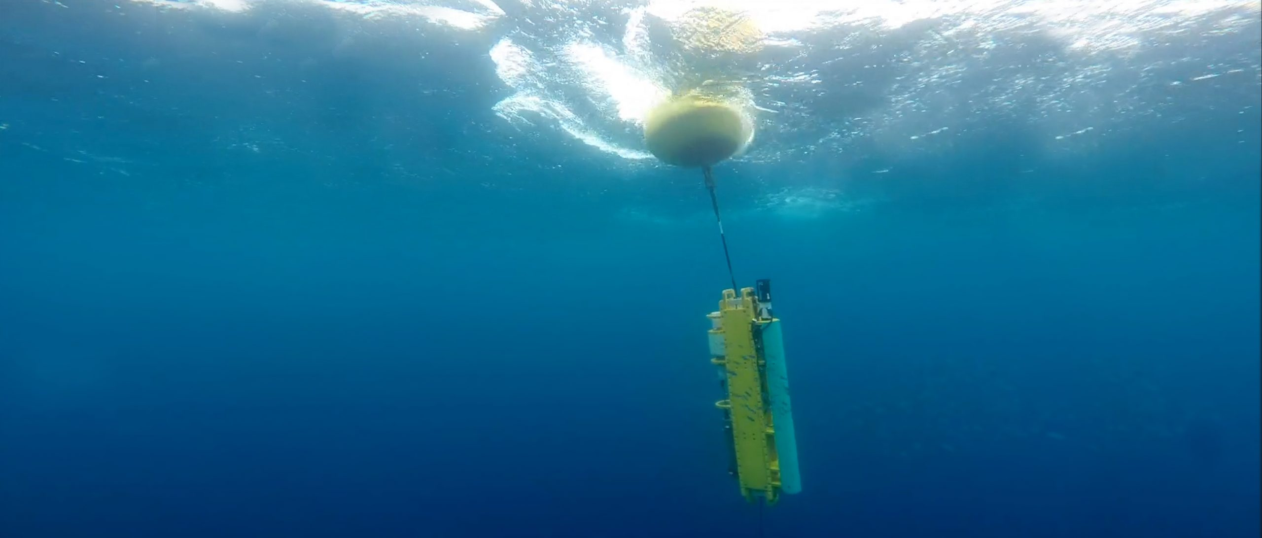 Yellow instrument dangling from buoy in blue water